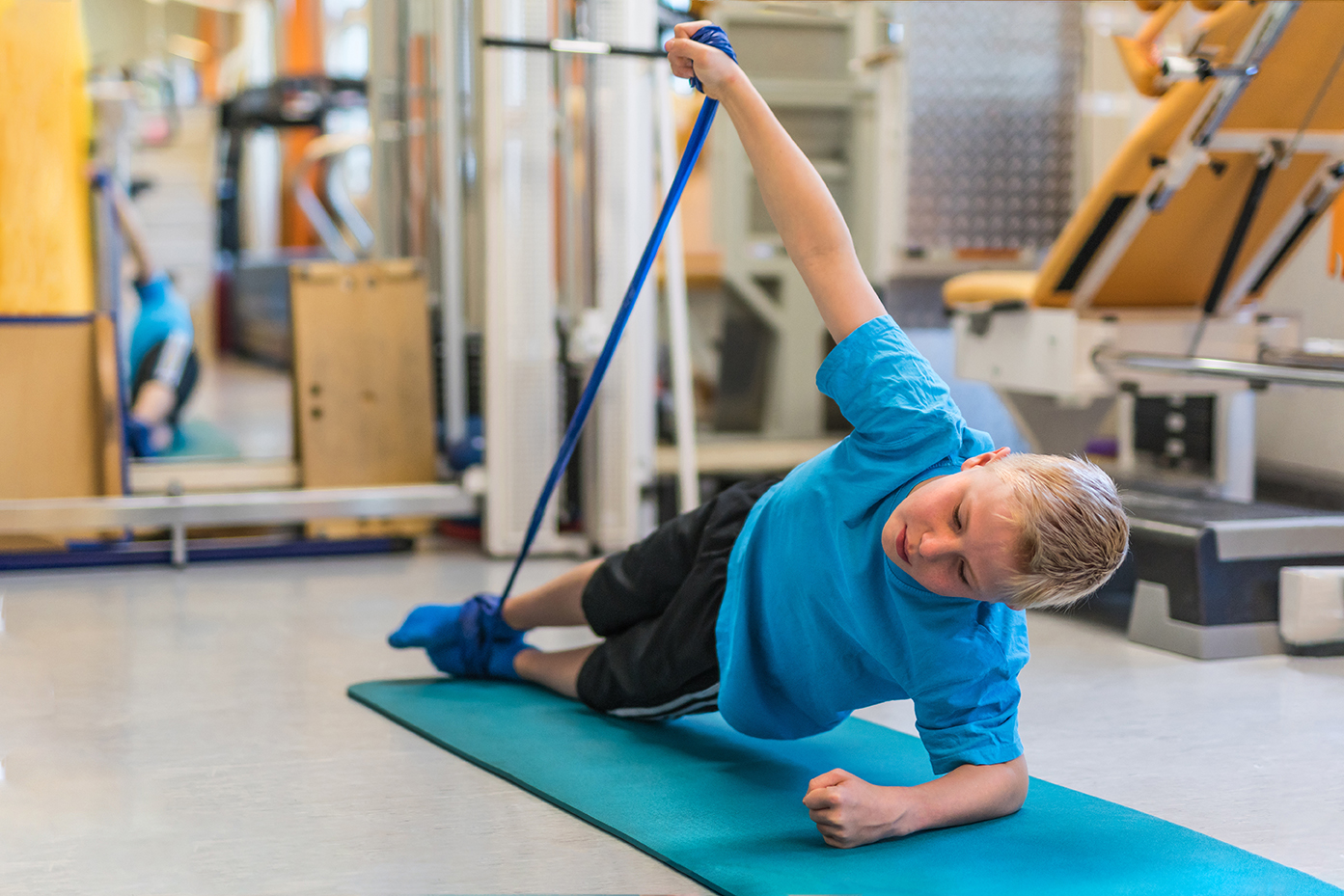 Kind bei der Physiotherapie trainiert mit einem Physiotape auf e